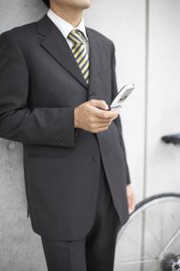 携帯電話を見るビジネスマンと自転車 FYI01129362