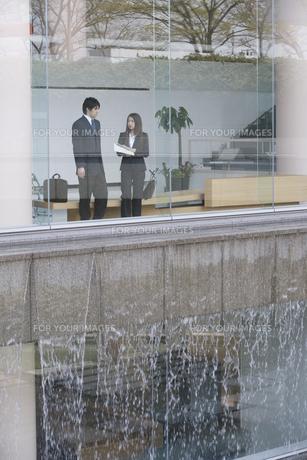 窓越しのビジネスマンとビジネスウーマン FYI01141021
