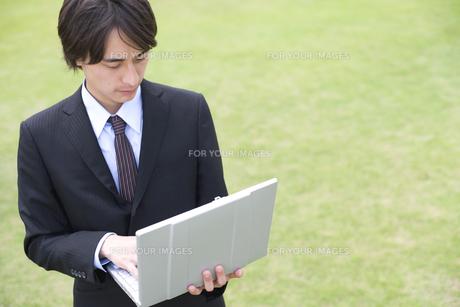 草原でパソコンをみるビジネスマン FYI01143871
