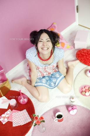 ピンクの雑貨に囲まれた女性 FYI01143941