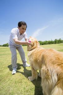 犬とボール遊びをするシニア男性 FYI01143946