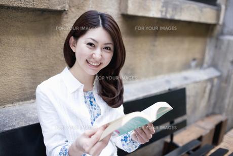ベンチに座り本を読む女性 FYI01143960