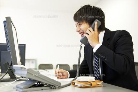 笑顔で電話をかけるビジネスマン FYI01144021