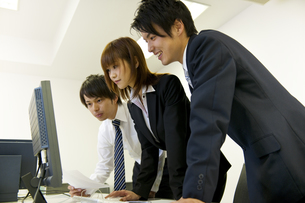 パソコンの画面を見るビジネスマン達の素材 [FYI01144776]
