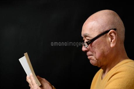 笑顔で読書をしているシニア FYI01164479