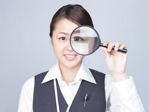 大きな虫眼鏡で目を拡大する女性 FYI01166308