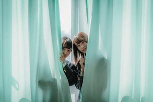 カーテンから顔を出す女子高生2人2 FYI01199612