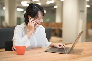 オフィスでPCを広げながら通話中のOL女性 FYI01216303