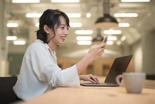 会社のデスクで携帯をいじるOL女性の写真素材 [FYI01216305]