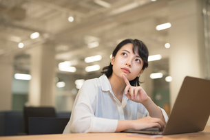 会社のデスクでPCを開いて考えこむOL女性 FYI01216306