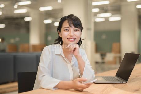 会社のデスクで談笑中のOL女性 FYI01216307