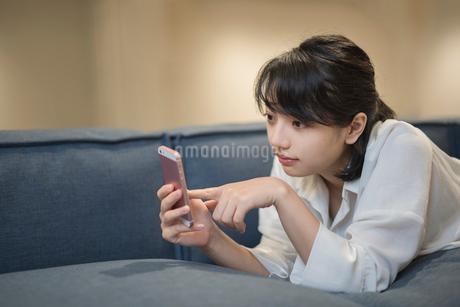 ソファに寝転がり携帯をいじるOL女性の写真素材 [FYI01216310]