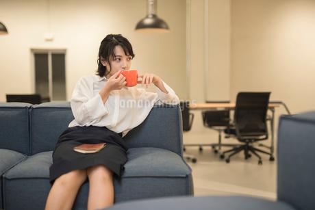 休憩中にソファに座り飲み物を飲むOL女性 FYI01216318