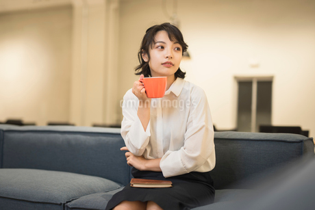 休憩中にソファに座り飲み物を飲むOL女性の写真素材 [FYI01216319]