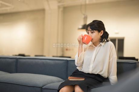休憩中にソファに座り飲み物を飲むOL女性 FYI01216320