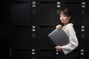 ロッカールームでPCを抱えるOL女性の写真素材 [FYI01216331]