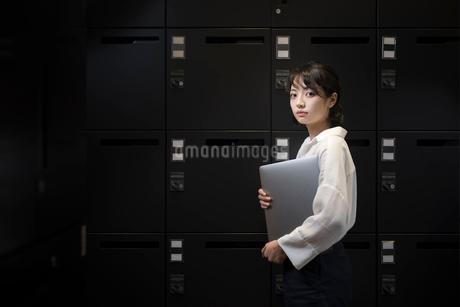 ロッカールームでPCを抱えるOL女性 FYI01216332