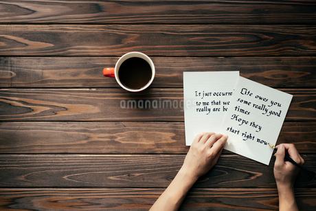 木目のテーブルの上にコーヒーカップを置いて便箋に文字を書いている所 FYI01216412