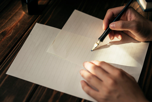 便箋とペンを持つ手の写真素材 [FYI01216425]
