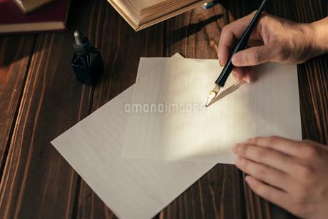 ペンを持つ手と紙と本と木目のテーブル。の写真素材 [FYI01216426]