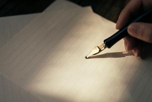 手紙を書く手と木目のテーブルの写真素材 [FYI01216427]