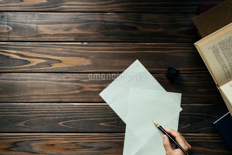 ペンを持つ手と紙と本と木目のテーブルの写真素材 [FYI01216432]