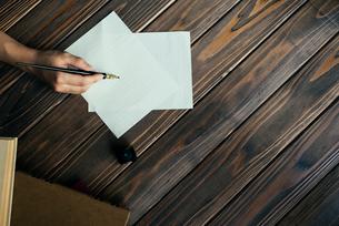 ペンを持つ手と本と木のテーブルの写真素材 [FYI01216433]