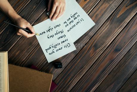 文字を紙に書く手と本と木のテーブルの写真素材 [FYI01216434]