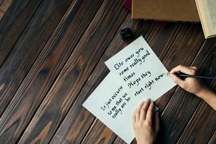 ペンを持って文字を書く手と、本と木目のテーブルの写真素材 [FYI01216435]