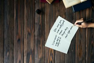 ペンを持って英字を書く手と、本と、木目のテーブル。の写真素材 [FYI01216436]