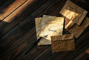 アンティークな封筒とMessageと書かれた紙の上にペンが置いてあるの写真素材 [FYI01216441]