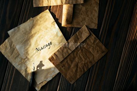 木目のテーブルにアンティークな封筒と便箋とペンが置いてあるの写真素材 [FYI01216442]