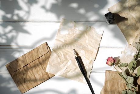 日差しの強い木漏れ日と、紙の上に置いたペンと、散りばめた封筒と紙と花 FYI01216574