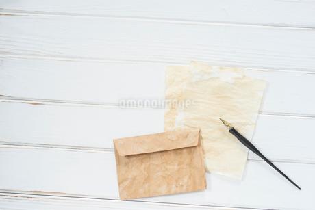 俯瞰構図の白木の背景とペンと紙と封筒。 FYI01216581