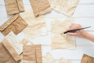 横構図の散りばめたアンティークな紙と封筒とペンを持つ手 FYI01216586