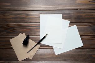 机の上に置いたペンと紙と封筒とインク FYI01216593