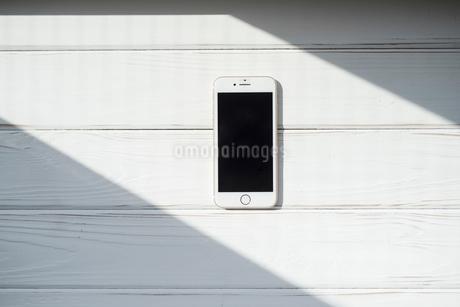 白い木目の上に置いたiPhoneの写真素材 [FYI01216610]
