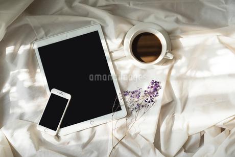 光が差し込む、iPadとiPhoneとコーヒーカップと花 FYI01216618