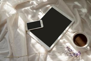 白い布の上に置いた、iPadとiPhoneとコーヒーカップと花 FYI01216620