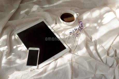 白い布の上に置いた携帯とiPadと花とコーヒーカップの写真素材 [FYI01216621]