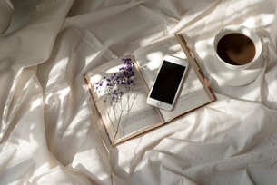 白い布の上に置いた本と携帯と花とコーヒーカップの写真素材 [FYI01216622]