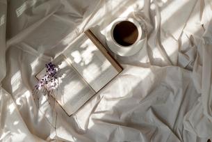 白い布の上に置いた本と花とカップの写真素材 [FYI01216625]