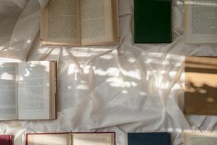 白い布の上に並べた本へ差し込む光の写真素材 [FYI01216627]