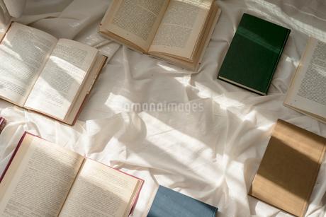 白い布の上に並べた本に差し込む光の写真素材 [FYI01216629]