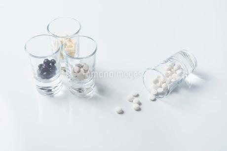 薬の入った4つのガラスコップと白背景 FYI01216649