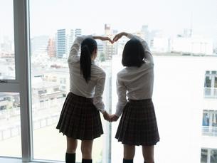 窓の外に向かってポーズをする2人の女子高校生 FYI01220695