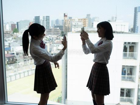窓の前で写真を撮る2人の女子高校生の写真素材 [FYI01220696]