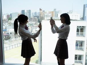 窓の前で写真を撮る2人の女子高校生 FYI01220696