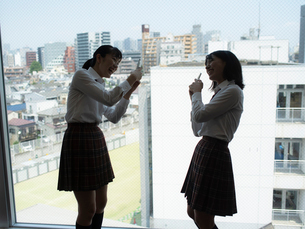 窓の前で写真を撮る2人の女子高校生の写真素材 [FYI01220697]