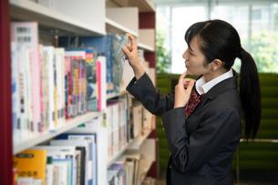 図書室で本を選ぶ女子高校生の写真素材 [FYI01220871]